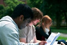 Students studying outside on the grass