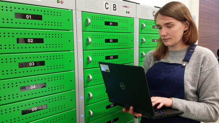 A student looks at a laptop while standing in front of the green laptop loan lockers in the Doug Ellis Suite at the Medical School.