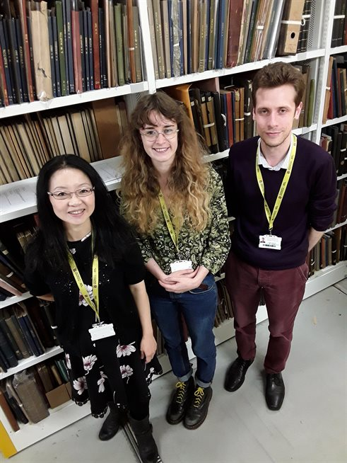 Three members of the thesis digitisation team stand in front of white shelves where the theses are stored.