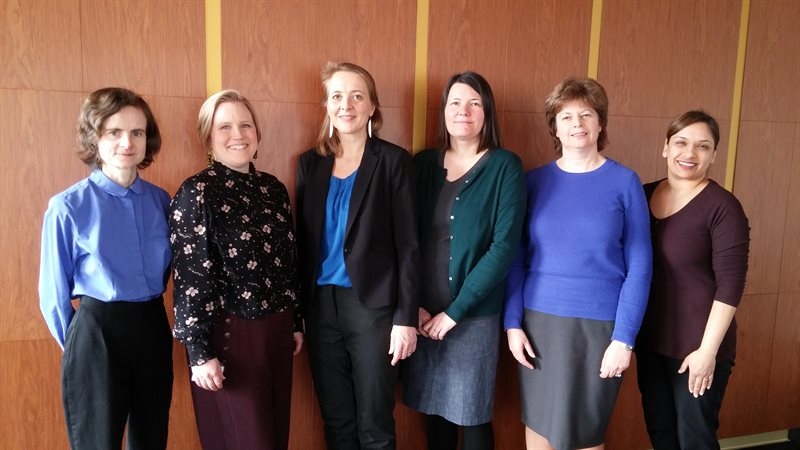 The six members of the Research Skills Team, standing in front of a wood panelled wall.