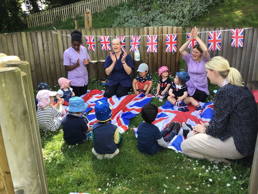 Nursery staff and children sitting around a union jack flag celebrating VE day