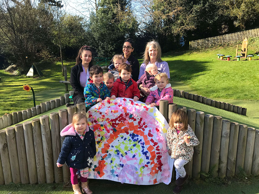 Rainbows group at the Elms posing with a painting