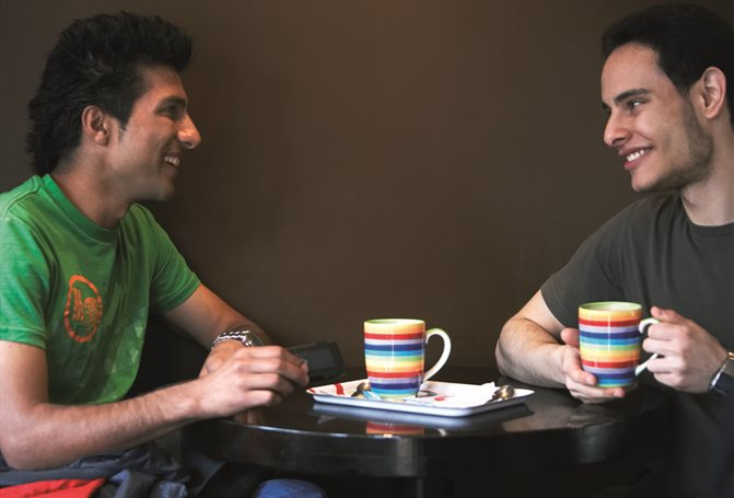 students in conversation with hot drinks